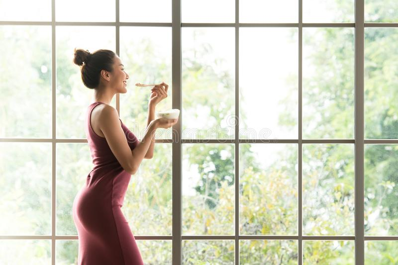 Healthy Asian woman standing and holding a bowl of yogurt looking relaxed and comfortable stock image