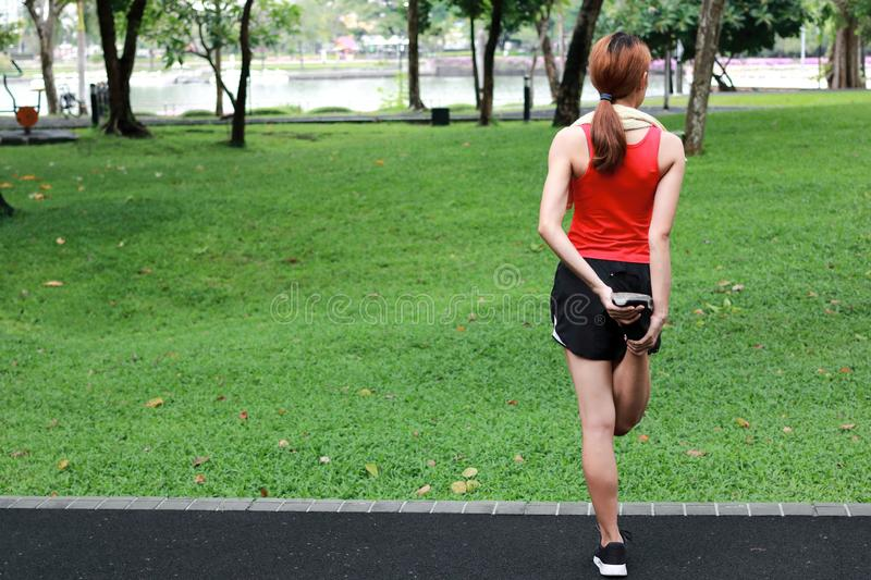 Healthy Asian woman stretching her legs before run in park. Fitness and exercise concept.  stock photography
