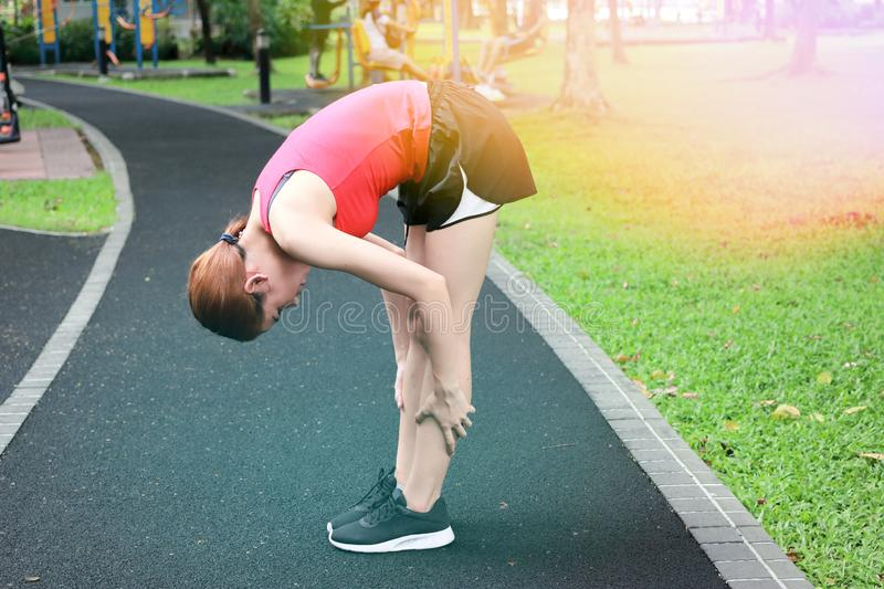 Healthy Asian woman stretching her legs before run in park. Fitness and exercise concept.  stock photos