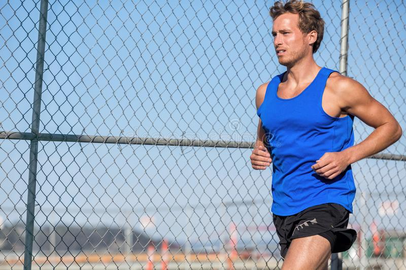 Healthy athlete runner man - urban city lifestyle. Young sports male running in grunge fence background outdoors in summer wearing. Blue tank top. Active living royalty free stock image