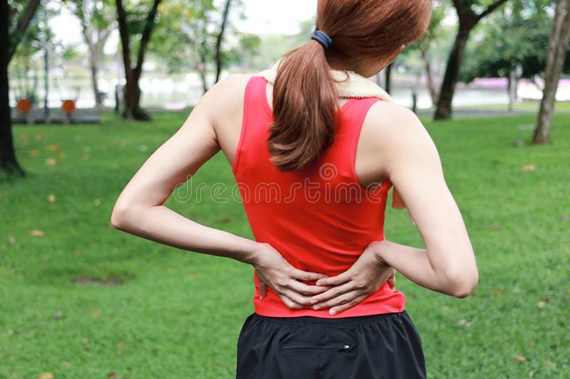 Healthy athlete suffering from back injury during run in the park. royalty free stock images