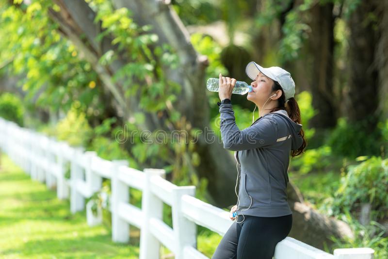 Healthy athletic asian woman is drinking pure water from the bottle refreshing herself after exercise stock photos
