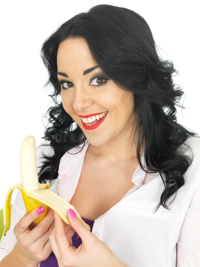 Attractive Young Healthy Woman With Long Black Curly Hair And Hispanic Or European Features Looking At Camera Smiling Peeling A Fresh Ripe Banana