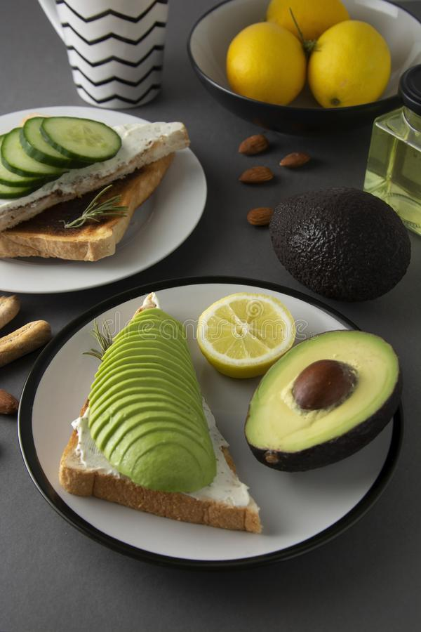 Healthy avocado breakfast. Sliced avocado on toast bread with spices, lemons. Dieting, food. Morning food stock photography