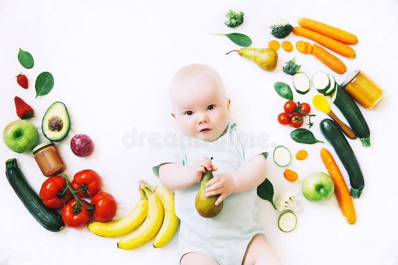 Healthy baby child nutrition, food background, top view. Healthy child nutrition, food background, top view. Smiling baby 8 months old surrounded with different royalty free stock photography