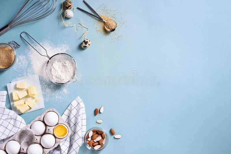 Healthy baking ingredients - flour, almond nuts, butter, eggs, biscuits over a blue table background. Bakery background frame. Top stock photos