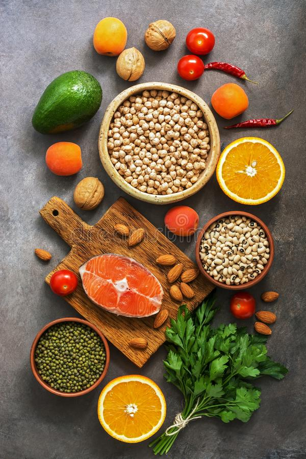 Healthy balanced food, salmon,legumes, fruits, vegetables, nuts, dark rustic background. The concept of healthy eating. Flat lay, stock photos