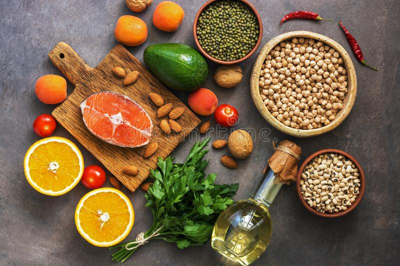 Healthy balanced food, salmon,legumes, fruits, vegetables, olive oil and nuts, dark rustic background. Overhead view, flat lay royalty free stock images