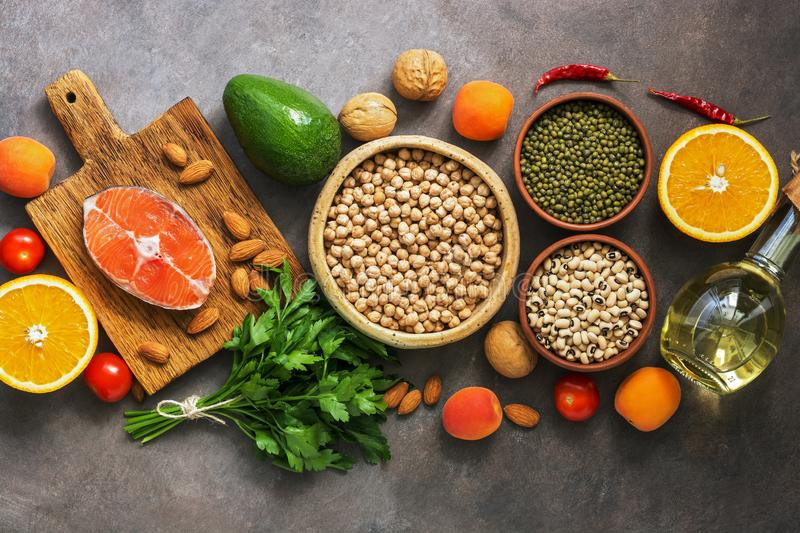 Healthy balanced food, salmon,legumes, fruits, vegetables, olive oil and nuts, dark rustic background. Overhead view, flat lay, stock photo