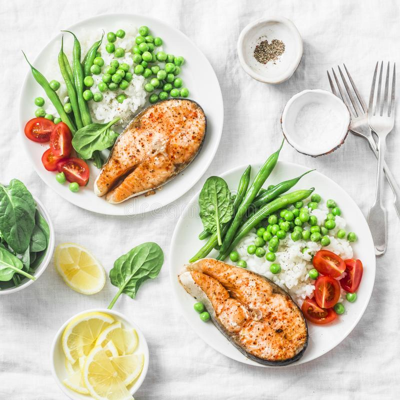 Healthy balanced mediterranean diet lunch - baked salmon, rice, green peas and green beans on a light background, top view stock photography