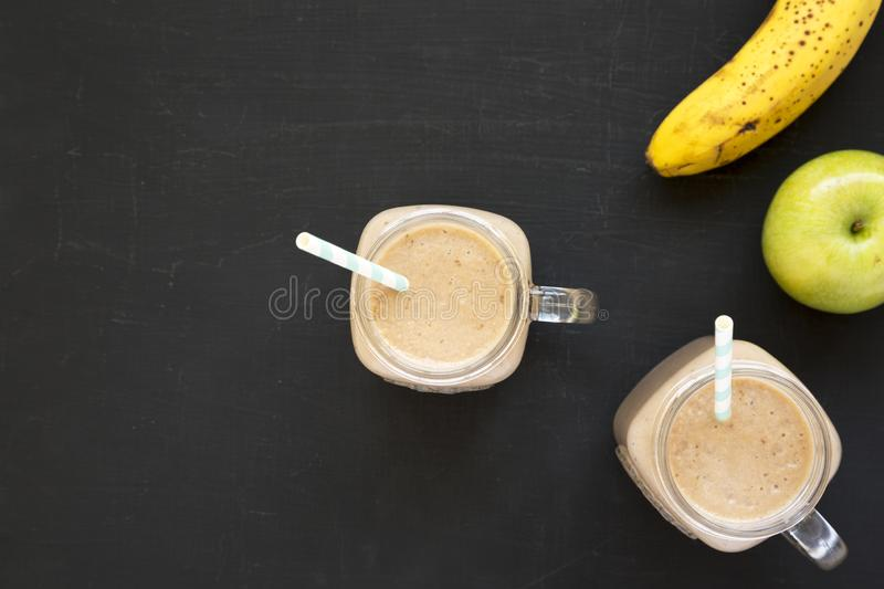 Healthy banana apple smoothie in glass jars over black surface, top view. Flat lay, from above, overhead. Space for text royalty free stock photography