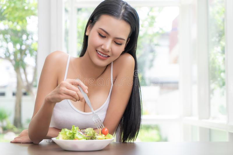 Healthy Beautiful woman is eating green vegetable salad for healthy lifestyle and beauty eating food concept in bright royalty free stock photos