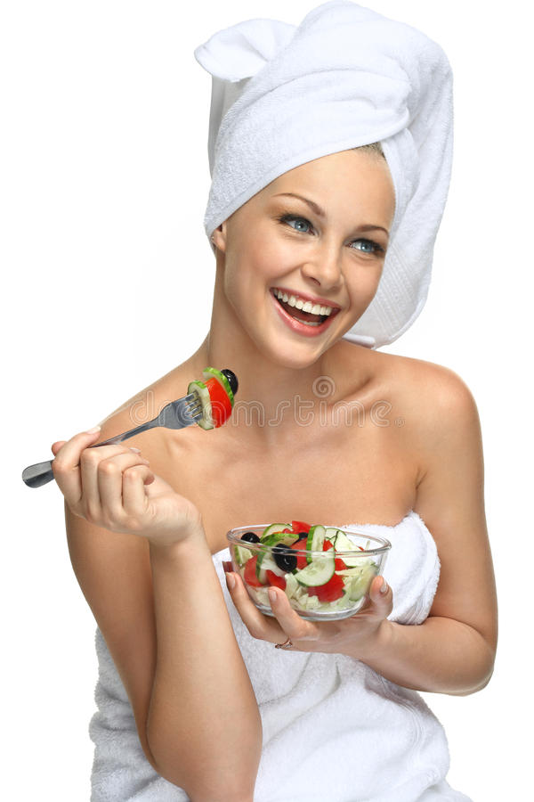 Healthy beauty. Beautiful blonde girl in towel eating fresh salad and smiling royalty free stock image