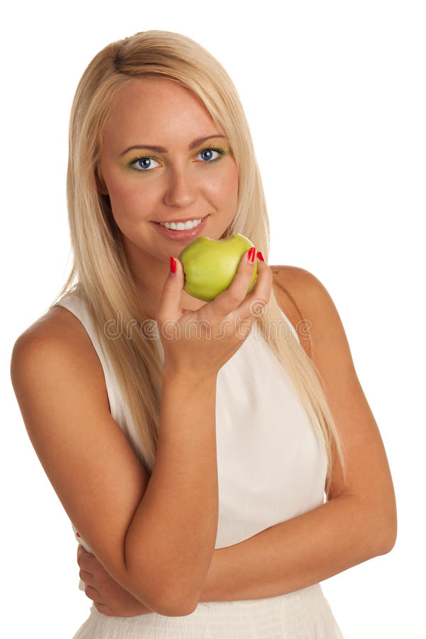Healthy beauty. Smiling young blond girl eating apple stock photography