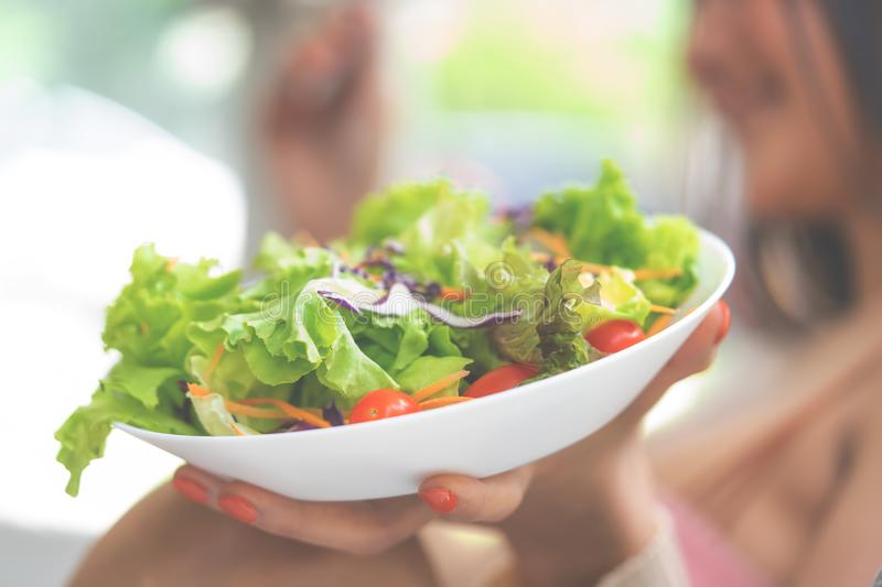 Healthy beauty young woman is eating green salad for healthy lifestyle food concept with fork and tomatoes going in her stock image