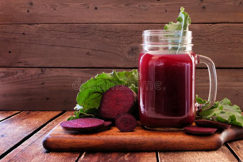 Beet juice in a mason jar glass on a platter against wood royalty free stock images