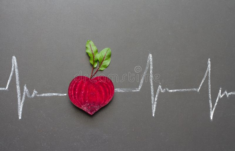 Healthy beetroot with heart shape and electrocardiogram on blackboard stock photography