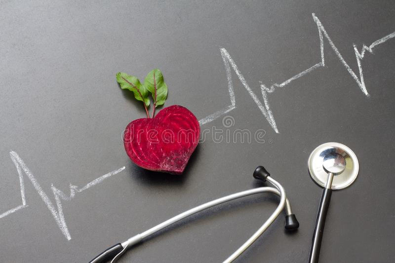 Healthy beetroot with heart shape and electrocardiogram on blackboard. Abstract royalty free stock photo