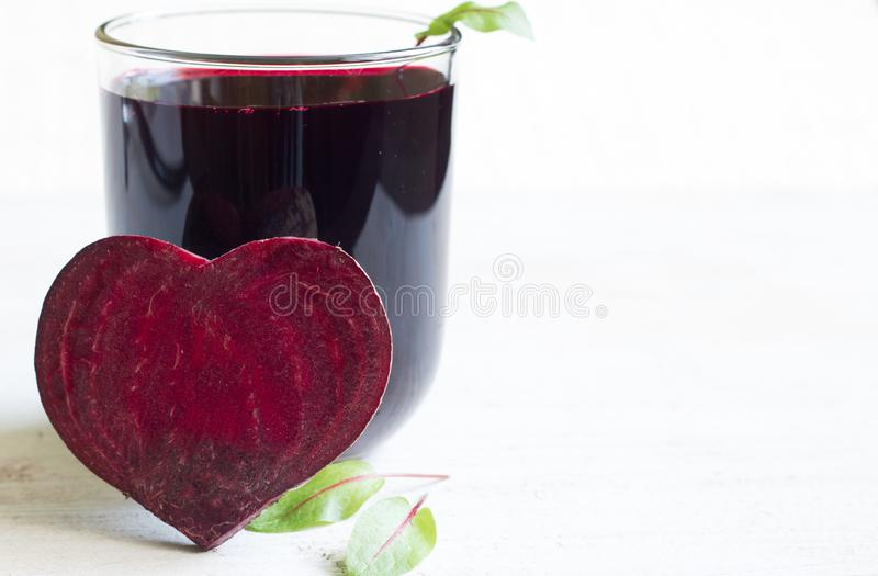 Healthy beetroot with heart shape and juice. On white plank royalty free stock images