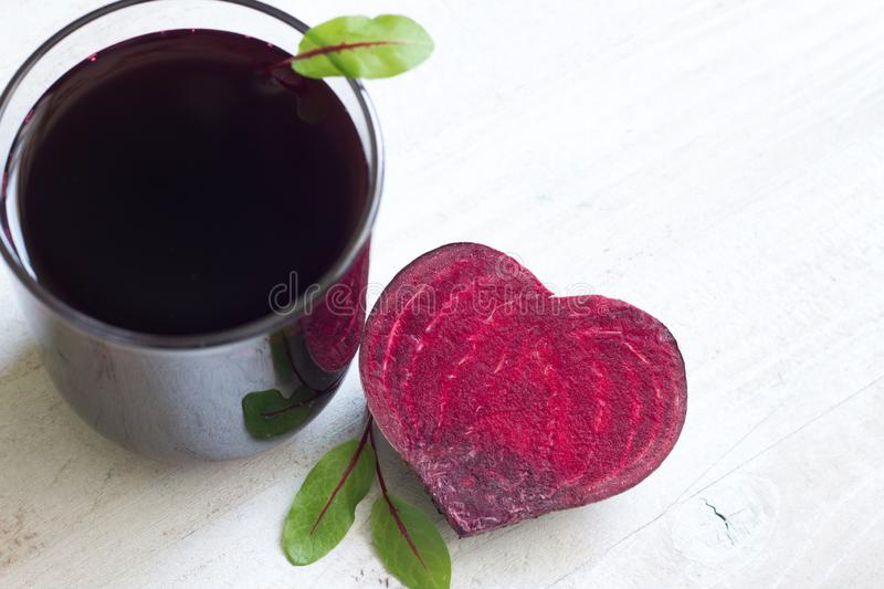 Healthy beetroot with heart shape and juice. On white plank stock images