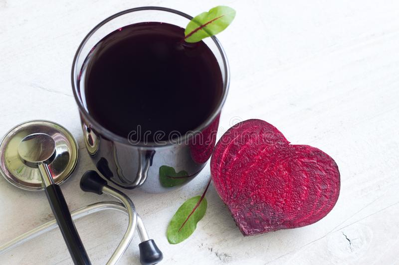 Healthy beetroot with heart shape and juice. On white plank stock photo