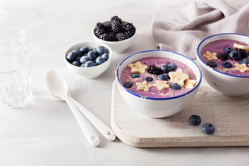 Healthy berry smoothie bowl with banana and sesame seed royalty free stock photography