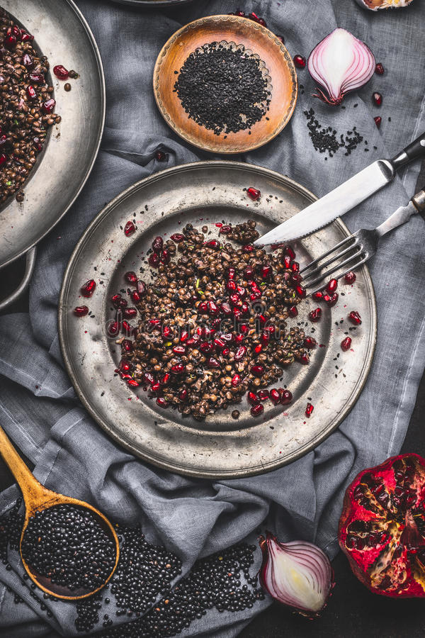 Download Healthy Black Beluga Lentil Salad With Pomegranate In Metal Plate With Cutlery On Dark Rustic Background With Cooking Ingredients Stock Photo - Image: 83701600