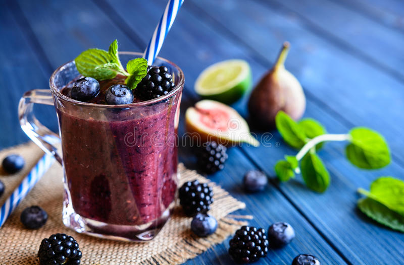 Healthy blackberry smoothie with figs, blueberry and lime. In a glass jar royalty free stock image