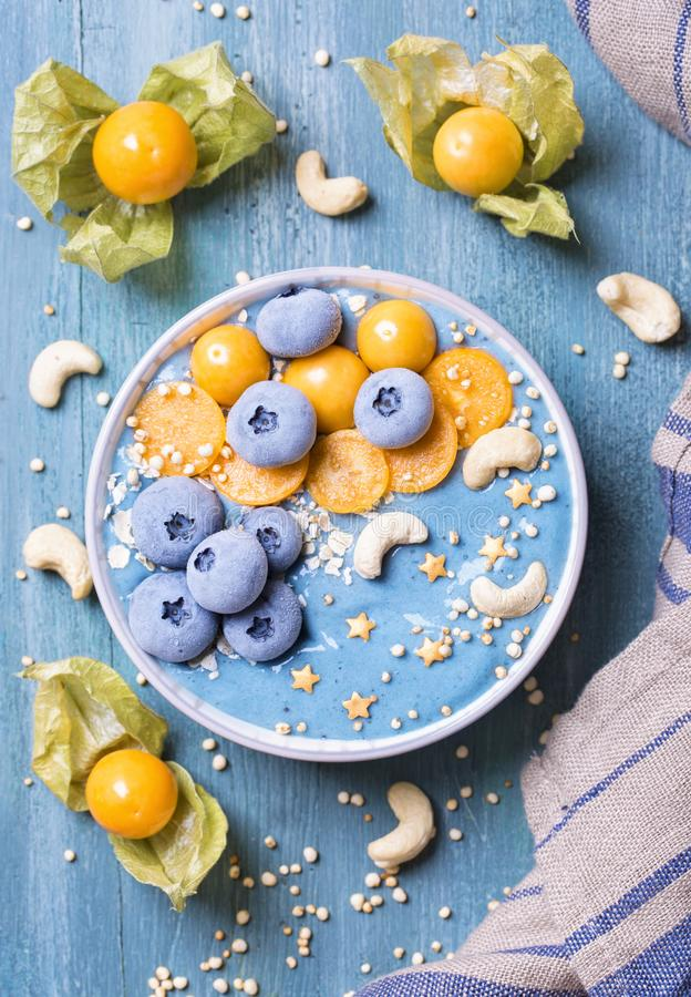 Healthy blue spirulina smoothie bowl. With blueberries and physalis royalty free stock image