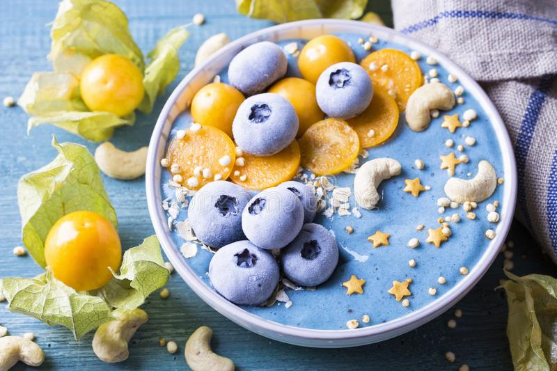 Healthy blue spirulina smoothie bowl. With blueberries and physalis royalty free stock images