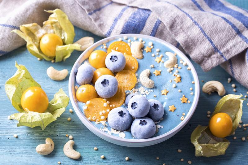 Healthy blue spirulina smoothie bowl. With blueberries and physalis stock photos