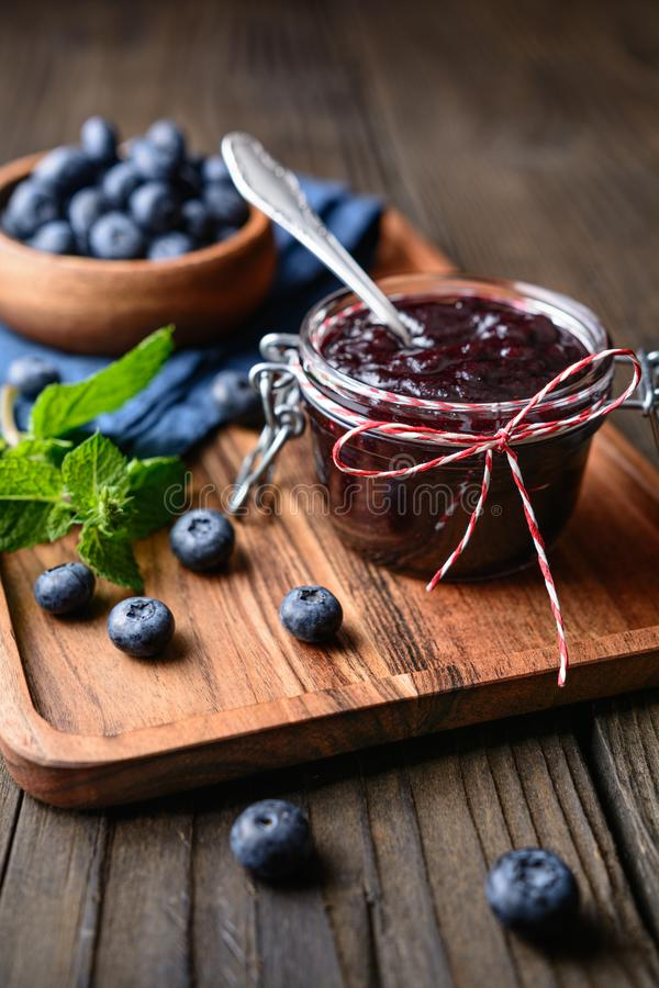 Healthy blueberry jam in a glass jar served with fresh berries. Served on wooden table stock images