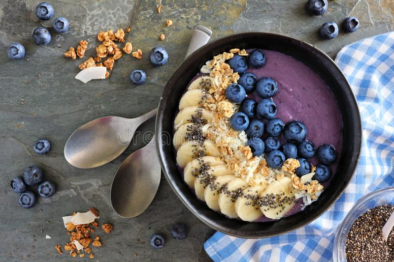 Blueberry smoothie bowl with coconut, bananas, chia seeds and granola, above view on a dark background. Healthy blueberry smoothie bowl with coconut, bananas royalty free stock image