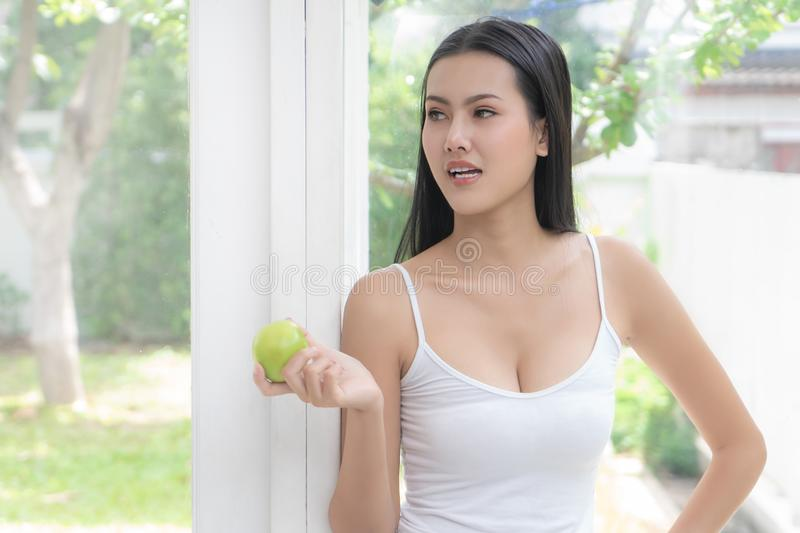 Healthy body beautiful asian woman eating green apple at home for healthy eating and healthy lifestyle concept royalty free stock photo