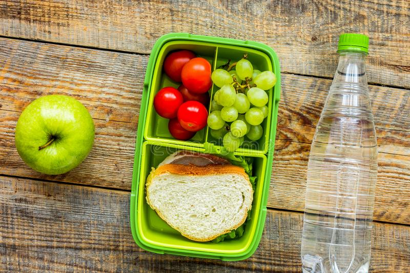 Healthy break with apple, grape and sandwich in lunchbox on home table flat lay royalty free stock images