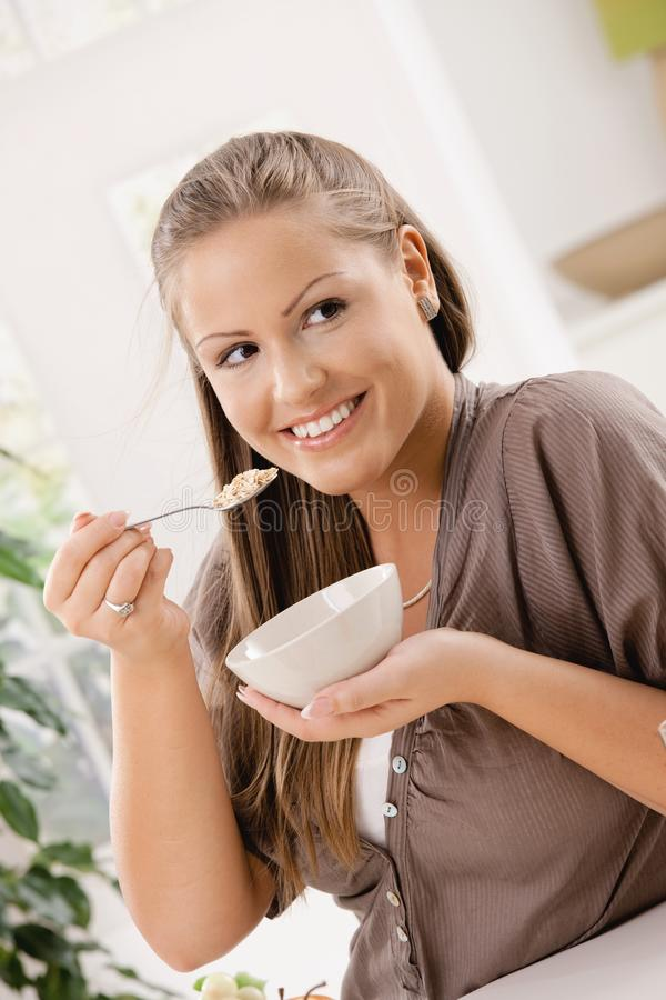 Healthy breakfast. Happy young woman eating breakfast cereal, smiling stock photo