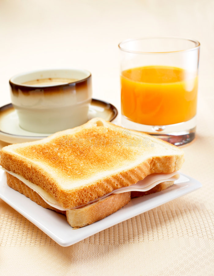Healthy breakfast. Sandwich, cup of coffee and fresh squeezed orange juice for breakfast. Shallow DOF stock image