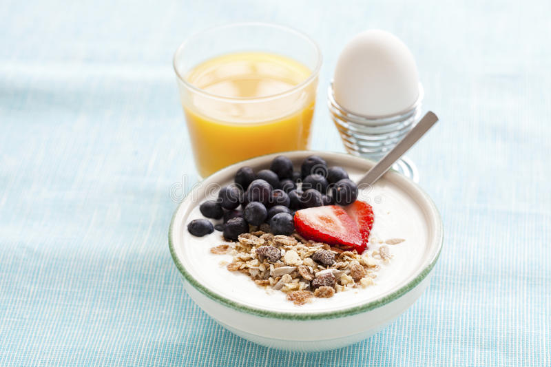 Healthy breakfast. Bowl of muesli with yoghurt, strawberries and blueberries, a boiled egg and a glass of orange juice for healthy breakfast royalty free stock photo