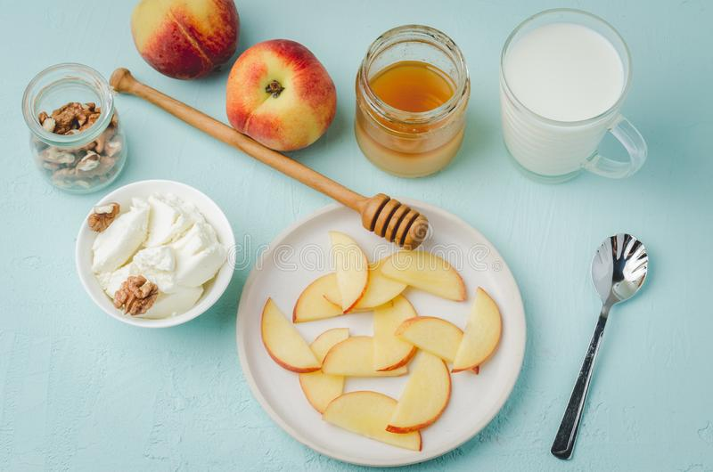 Healthy breakfast background. Peach, honey, milk, cottage cheese and walnut on a blue table. Top view stock image