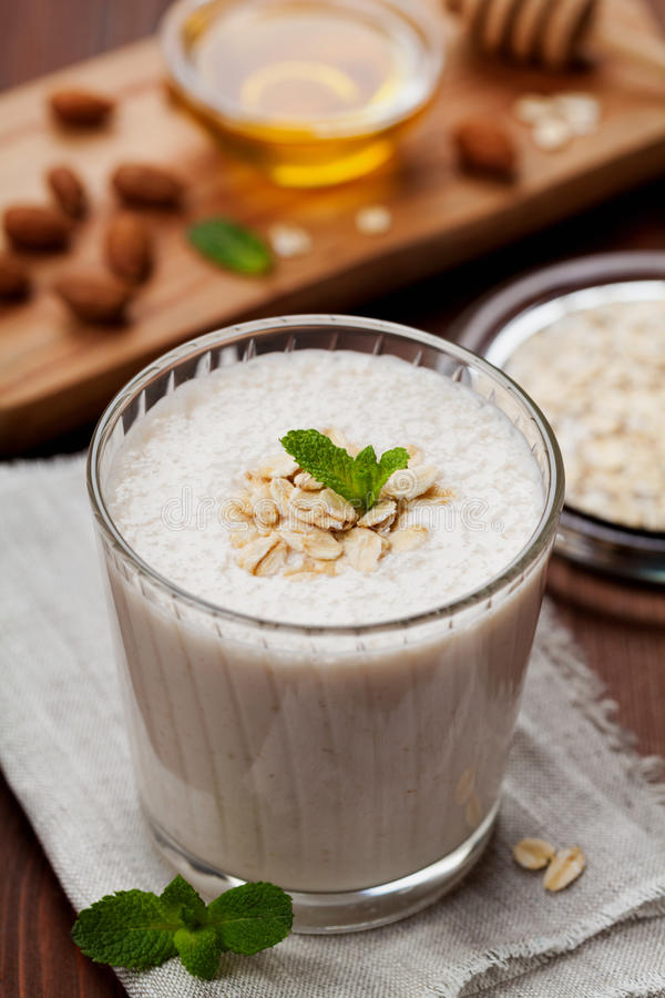 Healthy breakfast of banana smoothie or milkshake with oats and honey decorated mint leaves. On rustic surface stock photos