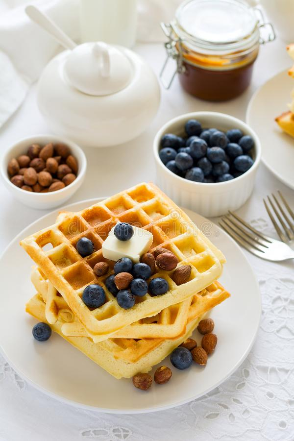 Healthy breakfast. Belgian waffles with butter, blueberry and nuts. On white tablecloth. Selective focus royalty free stock photo
