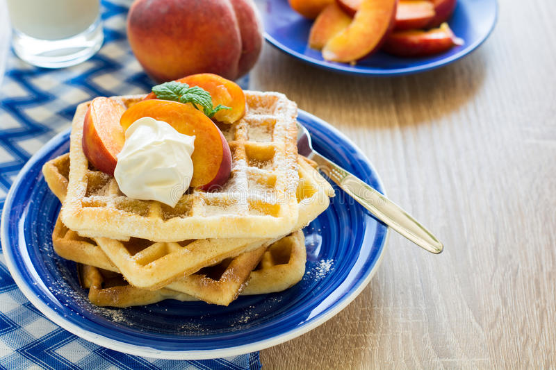 Healthy breakfast: Belgian waffles with peach slices and cream decorated mint leaves and blue napkin royalty free stock photo
