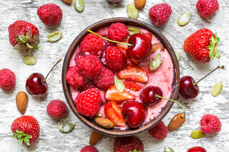 Healthy breakfast berry smoothie bowl topped with raspberry, strawberry, cherry, chia and pumpkin seeds stock photo