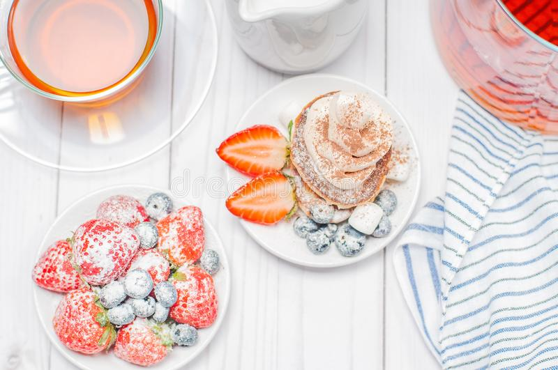 Healthy breakfast, black tea and homemade pancakes with fresh berries stock photos