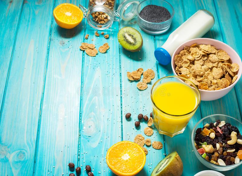 Healthy breakfast with bowl of cereal, orange juice, granola, milk, jam and fruits on blue wood background. Balanced diet. royalty free stock images