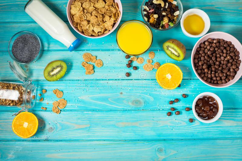 Healthy breakfast with bowl of cereal, orange juice, granola, milk, jam and fruits on blue wood background. Balanced diet. Copy space and top view stock images