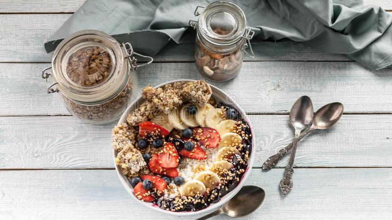 Healthy breakfast bowl: Cottage cheese, granola, bananas, strawberries, blueberries and puffed rice. Wooden table background. Top royalty free stock photography