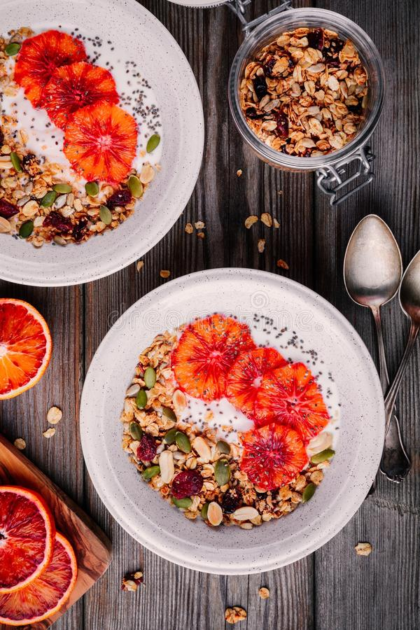 Healthy breakfast bowl of homemade granola with fresh yogurt and blood slices oranges stock images