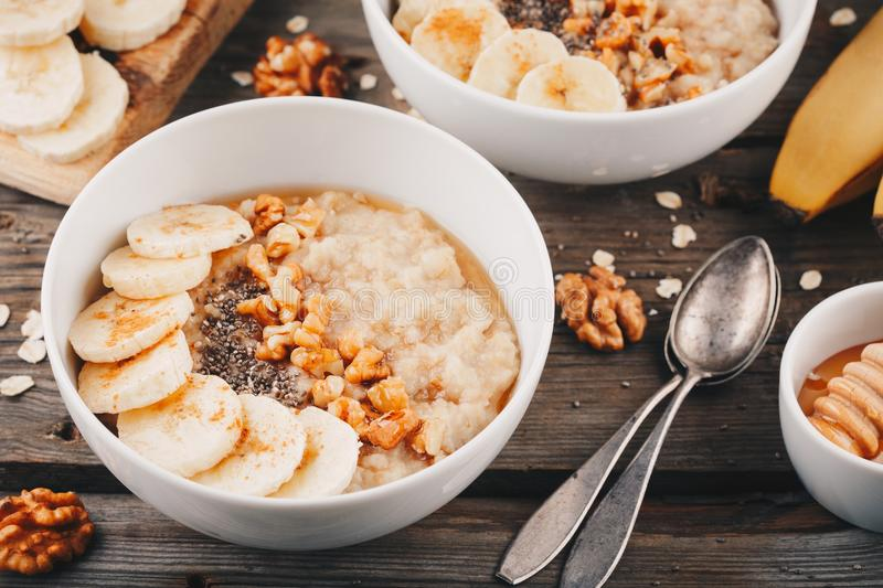 Healthy breakfast bowl. oatmeal with banana, walnuts, chia seeds and honey stock images