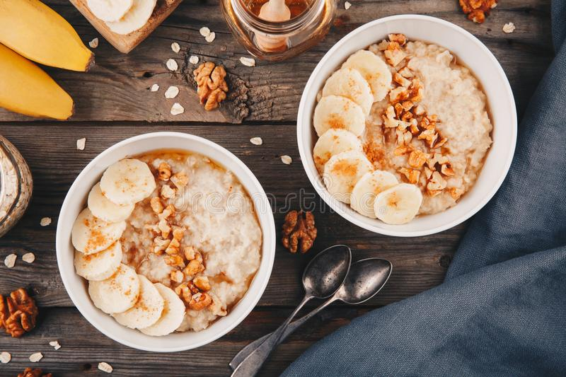 Healthy breakfast bowl. oatmeal with banana, walnuts, chia seeds and honey stock photos